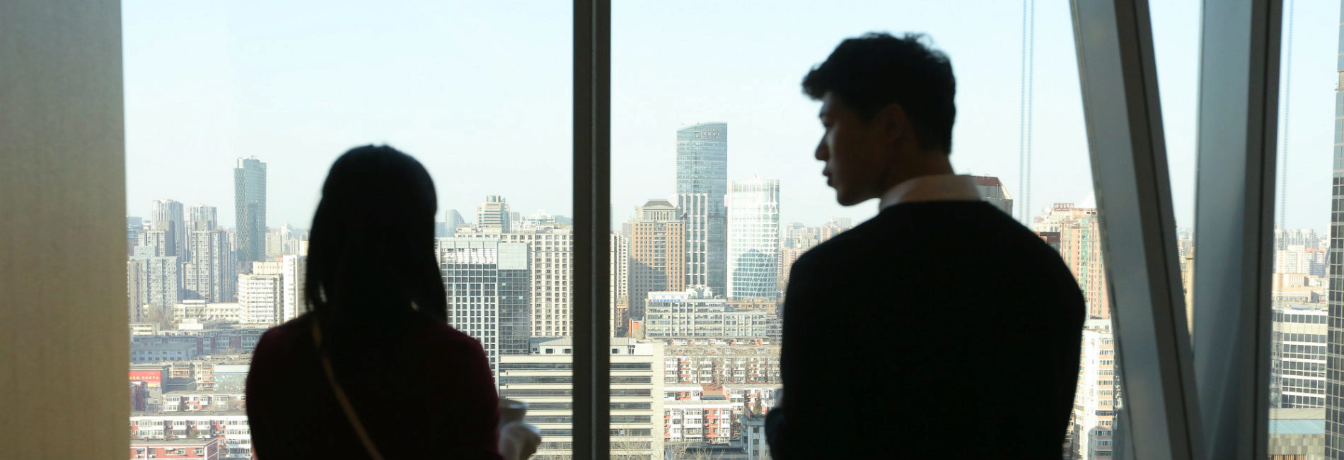 Young man and women looking out at Beijing from Penn Wharton China Center
